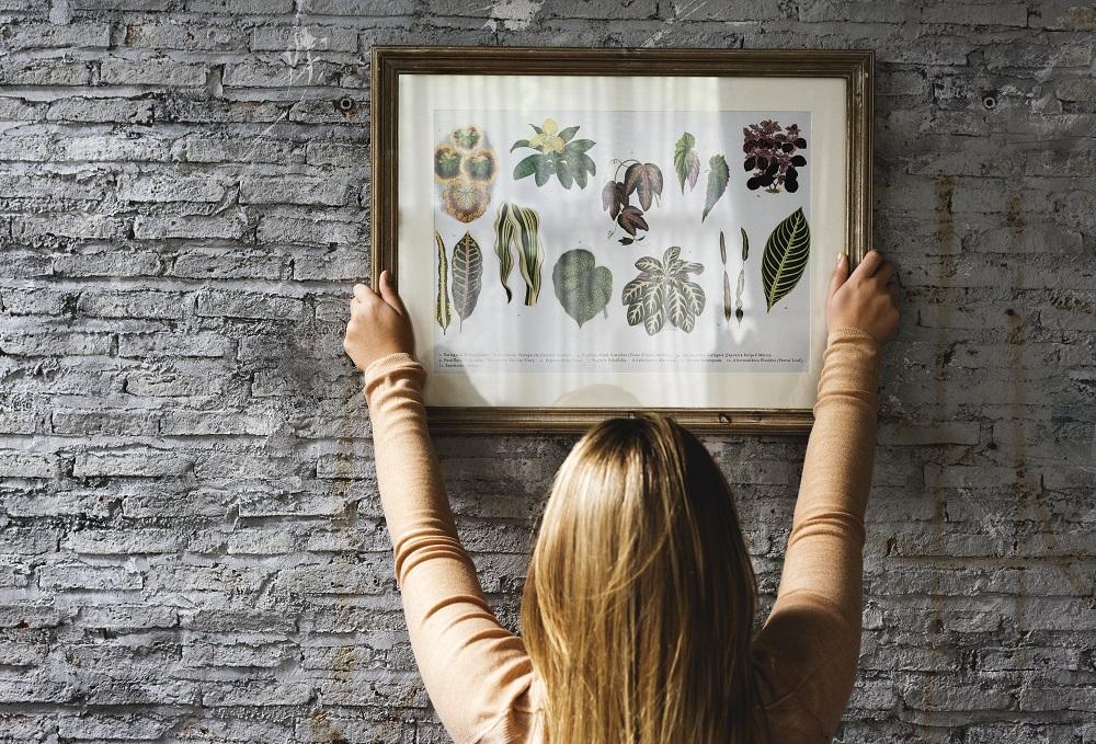 Kobieta wiesza na ścianie obrazek