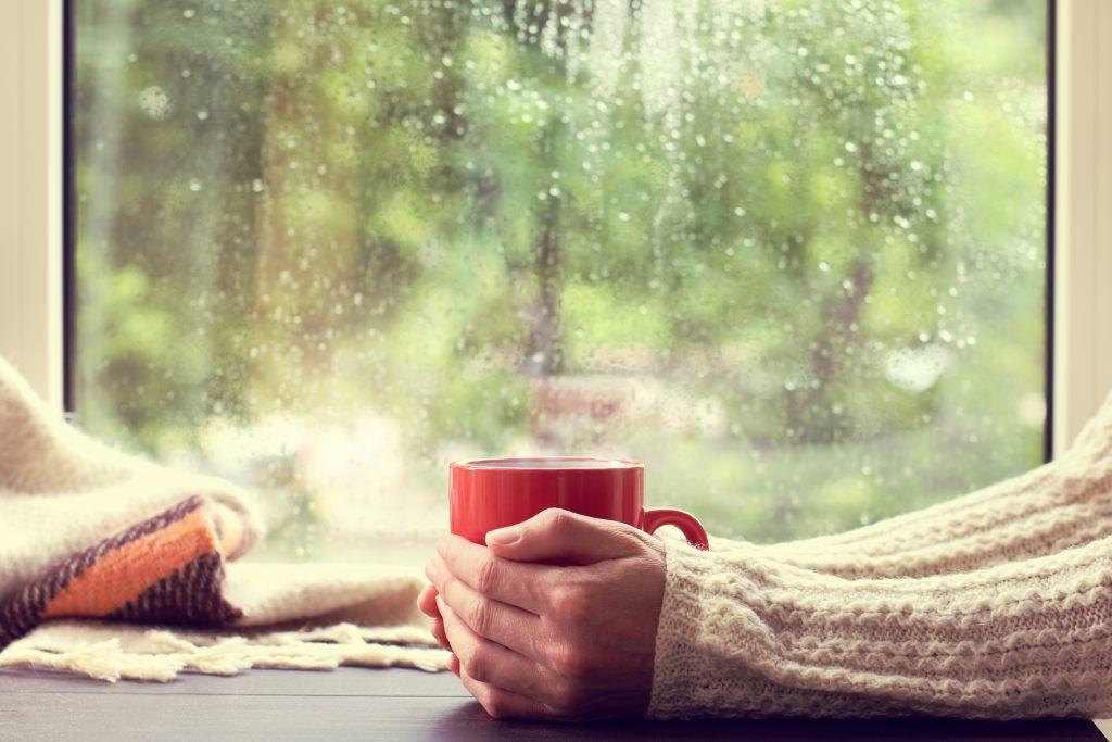 kubek-herbata-okno-deszcz-dłonie-zimno-uszczelnienie-ciepły-napój
