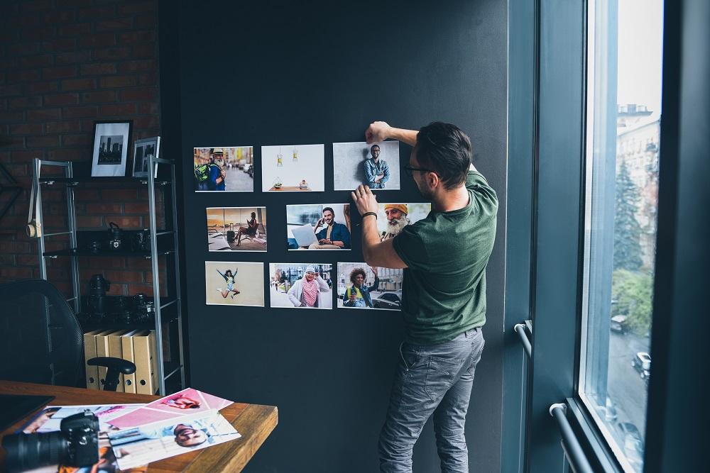 Mężczyzna przykleja zdjęcia do ściany