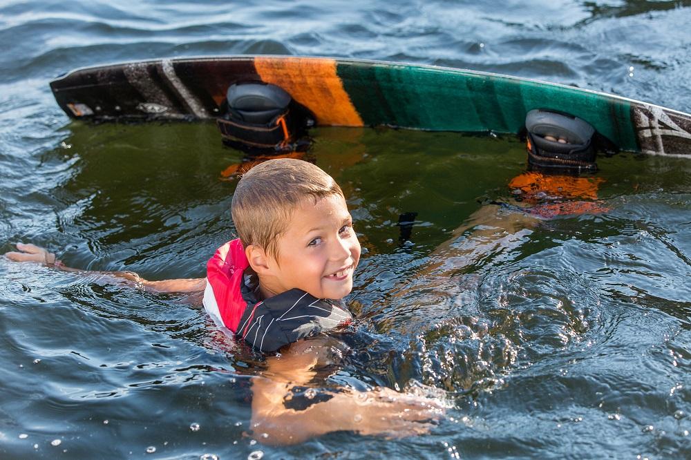 Chłopiec w wodzie z deską wakeboardową.