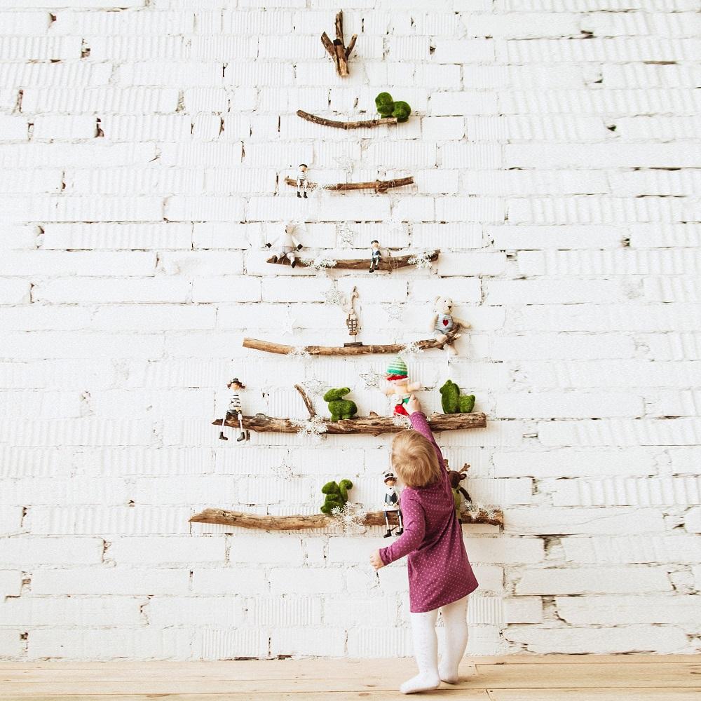 Dziecko przy choince z patyków na ścianie