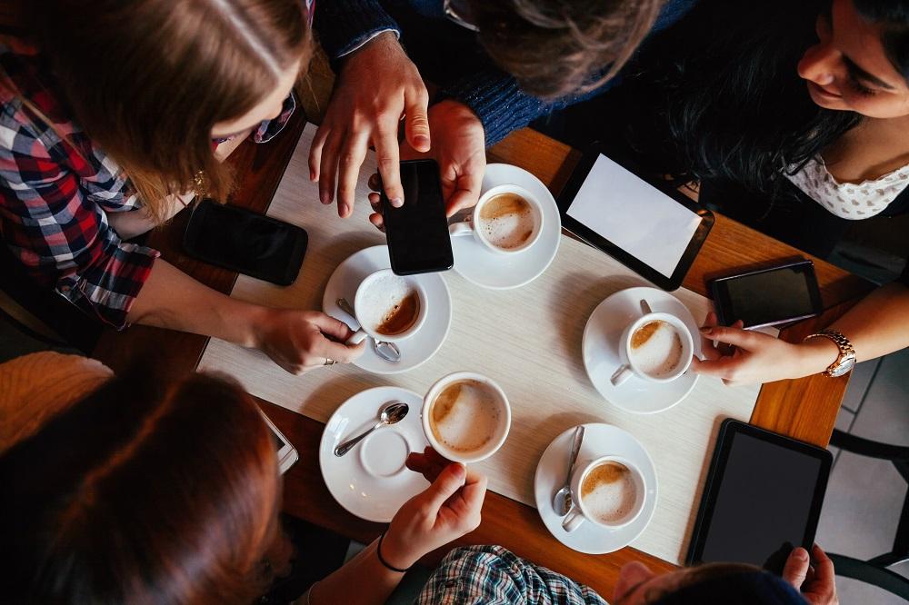 Grupa przyjaciół przy kawie w kawiarni