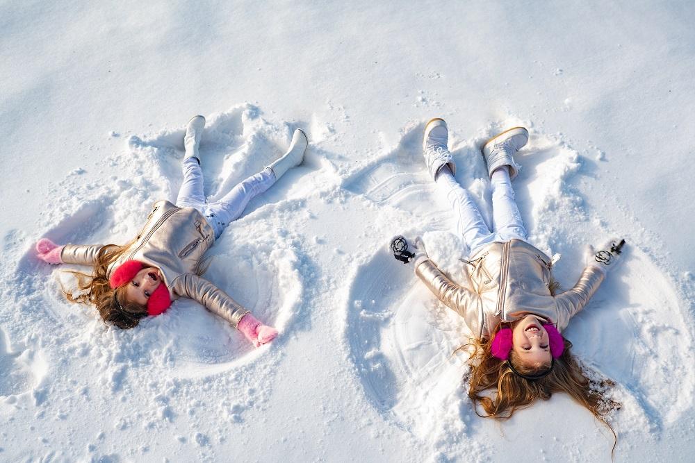 Dziewczynki na śniegu robią aniołki