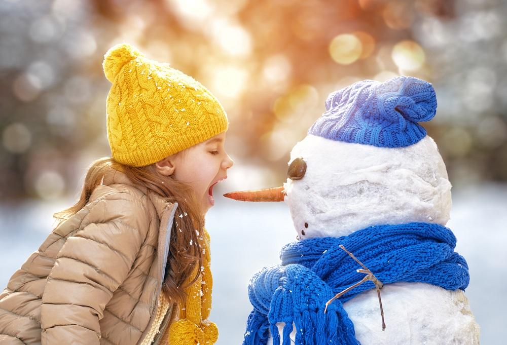 Dziewczynka gryzie w nos bałwanka