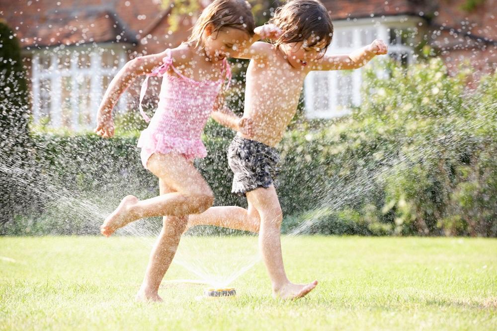 Dzieci biegną przez ogrodowy spryskiwacz