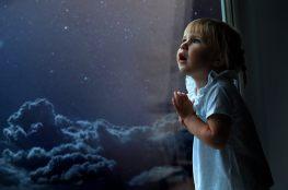 Dziecko patrzy przez okno na niebo