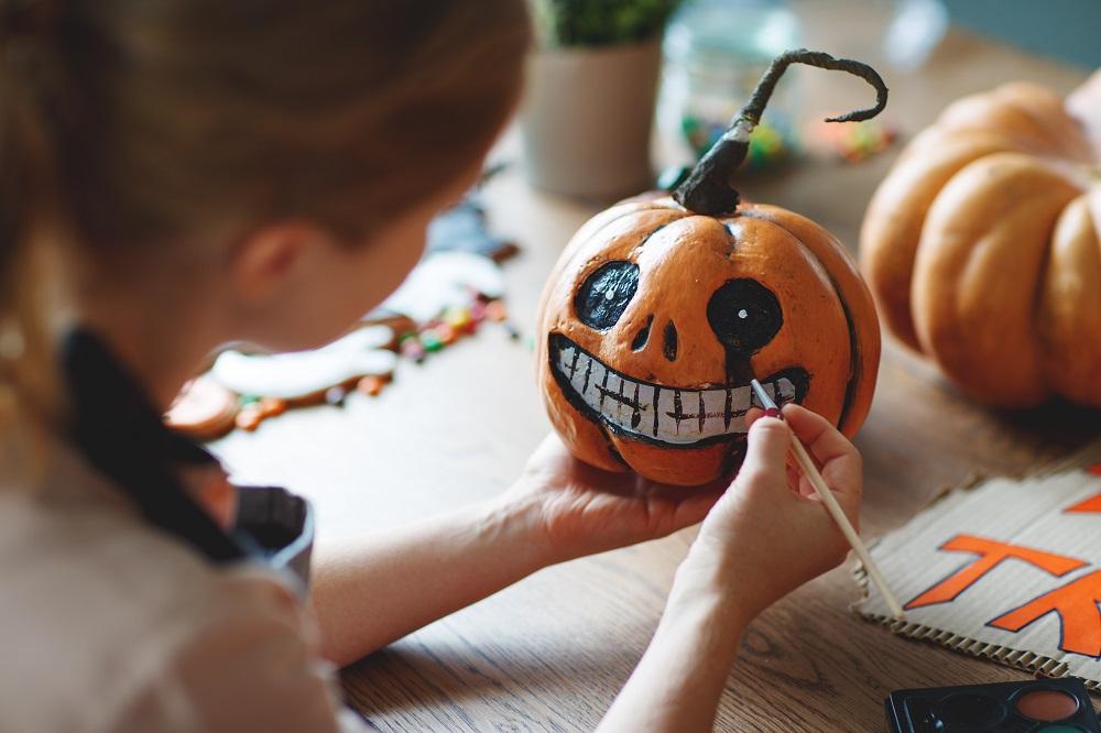 Kobieta maluje dynię na Halloween