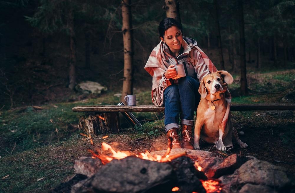 Pies i kobieta przy ognisku