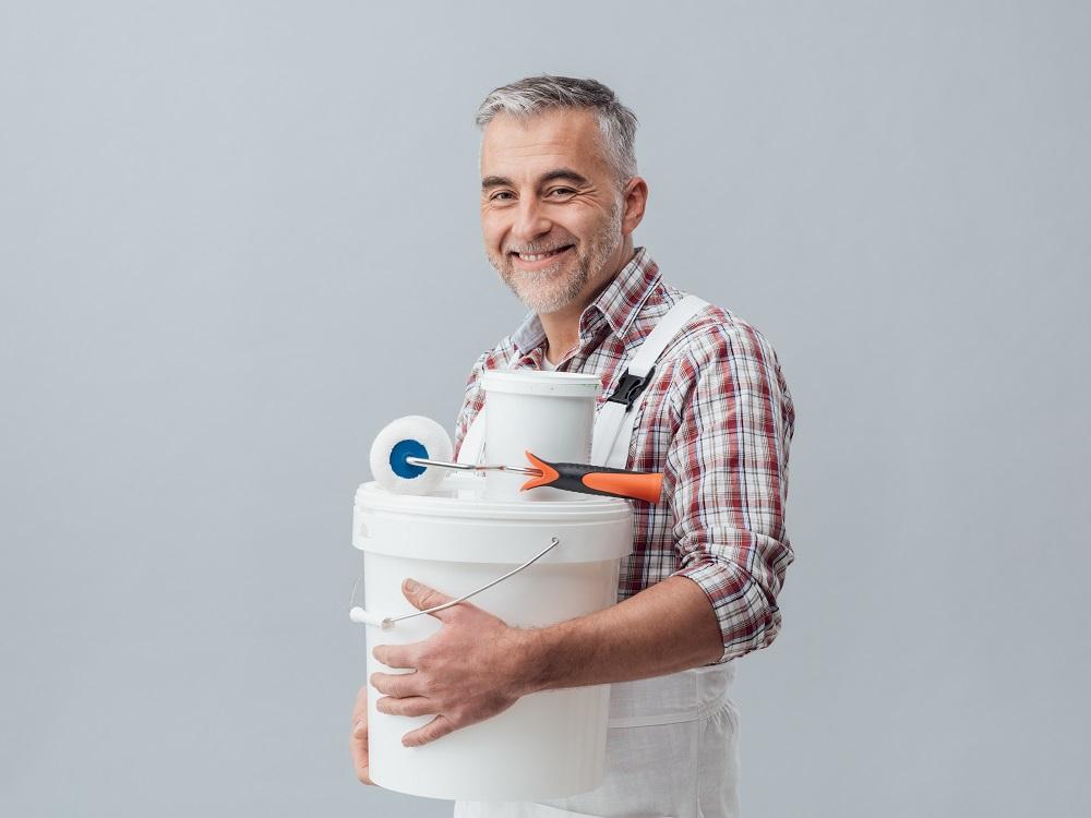 Uśmiechnięty mężczyzna z akcesoriami do remontu.