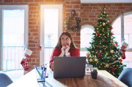 Kobieta siedzi przed komputerem, w tle sztuczna choinka